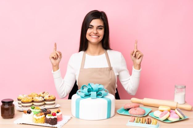 Pasticcere con una grande torta in una tabella sopra il rosa isolato che indica una grande idea