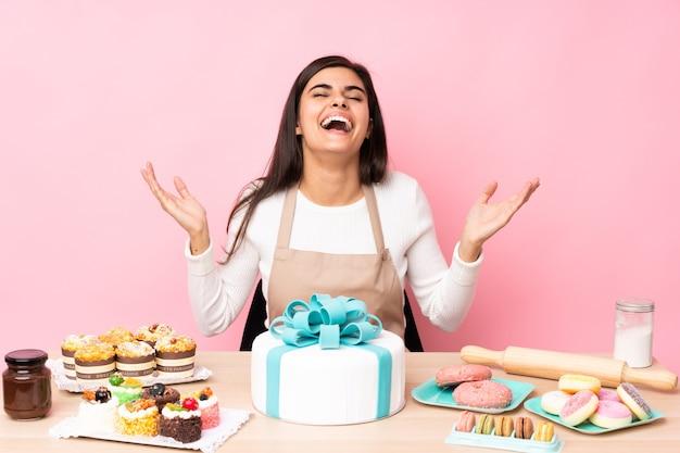 Pasticcere con una grande torta in una tabella sopra il rosa isolato che sorride molto