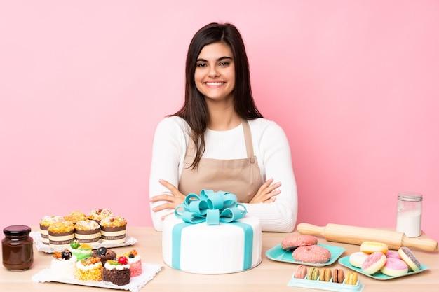 Pasticcere con una grande torta in un tavolo sopra il muro rosa isolato con le braccia incrociate e guardando avanti