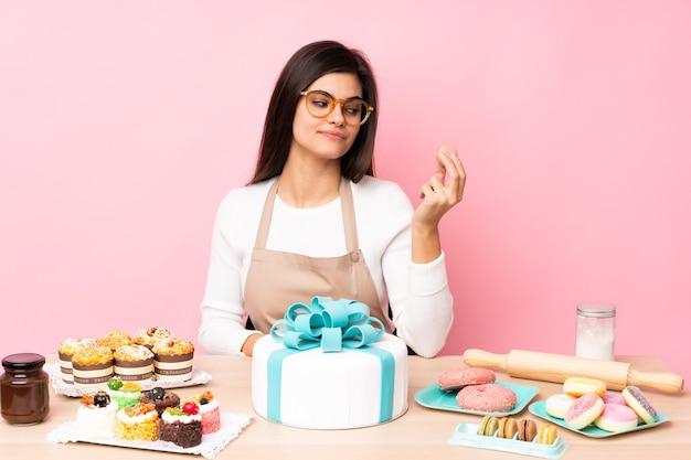 Pasticcere con una grande torta in una tabella sopra il rosa isolato