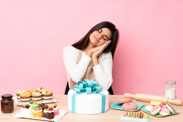 Pasticcere con un grande dolce in una tavola sopra la parete rosa che fa gesto di sonno nell'espressione adorabile