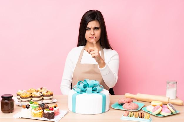 Pasticcere con una grande torta in una tabella
