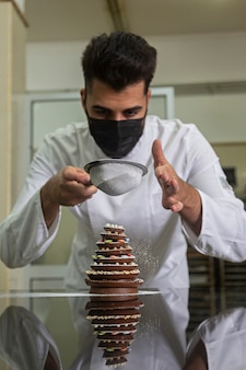 Pasticcere con una maschera che rifinisce un albero di natale di cioccolato.