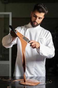 Pasticcere che lavora alla tempera del cioccolato sulla tavola di marmo