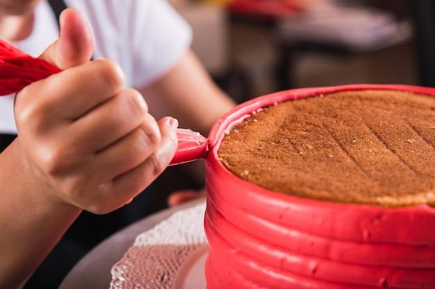 Mani di pasticceria, decorando una torta con una manica di crema.