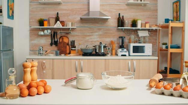 Ingredienti della pasticceria pronti per la cottura nella cucina moderna senza nessuno. moderna sala da pranzo vuota attrezzata con utensili, uova fresche e farina di frumento in una ciotola di vetro per torte e pane fatti in casa