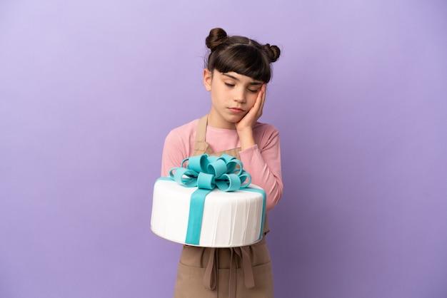 Pasticceria bambina che tiene una grande torta isolata su sfondo viola con mal di testa