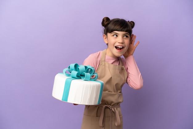 Pasticceria bambina che tiene una grande torta isolata su viola ascoltando qualcosa mettendo la mano sull'orecchio