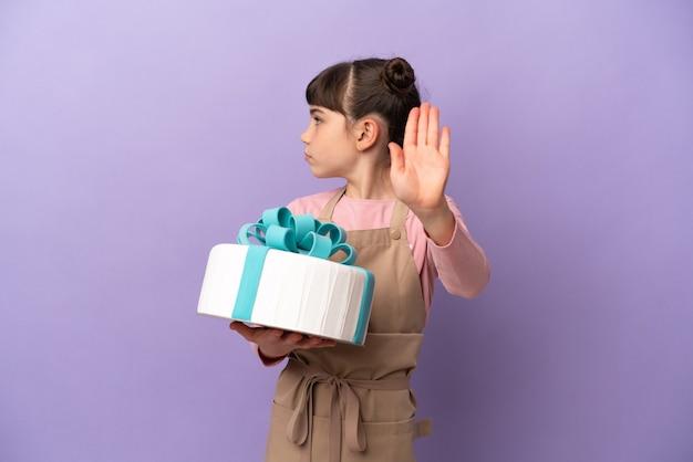 Pasticceria bambina che tiene una grande torta isolata sulla parete viola che fa gesto di arresto e deluso