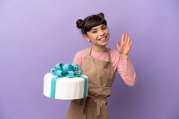 Pasticceria bambina che tiene una grande torta isolata sulla parete viola che saluta con la mano con l'espressione felice