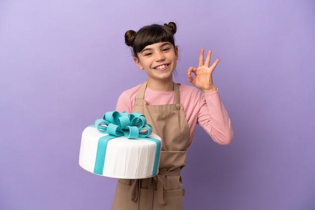 Pasticceria bambina che tiene una grande torta isolata sulla parete viola che mostra segno giusto con le dita