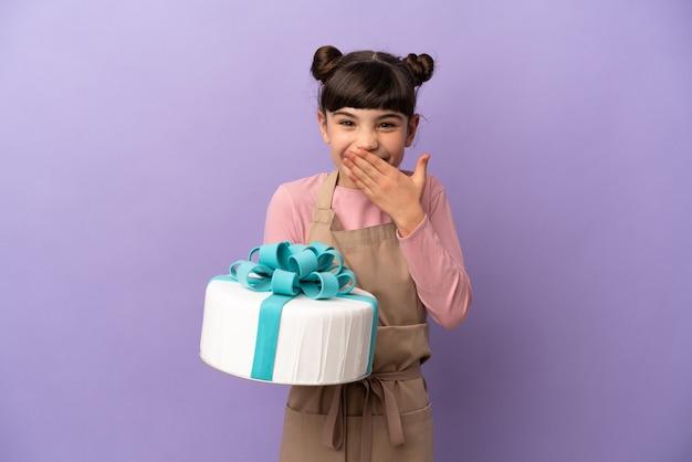 Bambina della pasticceria che tiene una grande torta isolata