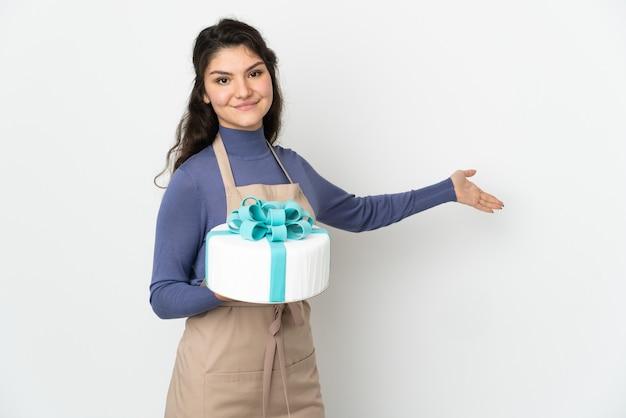 Pasticcere chef russo che tiene una grande torta isolata sul muro bianco che estende le mani a lato per invitare a venire