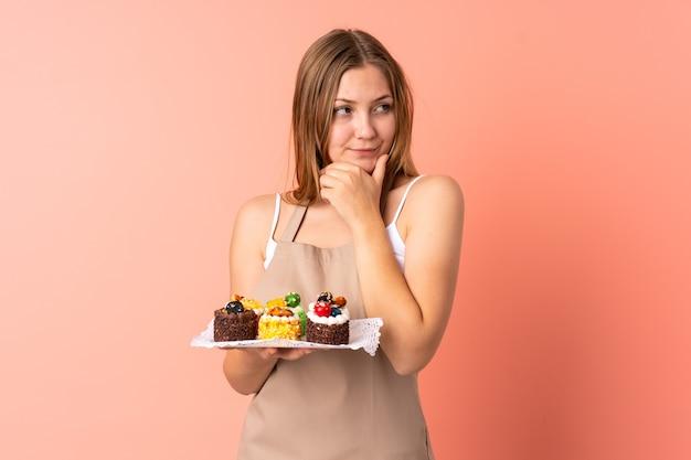 Cuoco unico ucraino della pasticceria che tiene un muffin