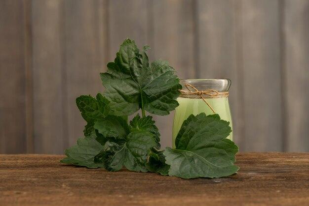 Patchouli o pogostemon cablin benth, foglie verdi e olio su un vecchio legno.