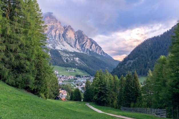 Un sentiero che conduce attraverso un prato alpino al villaggio di corvara ai piedi delle dolomiti in italia