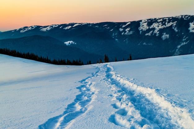 Percorso con impronte nella neve in montagna invernale.