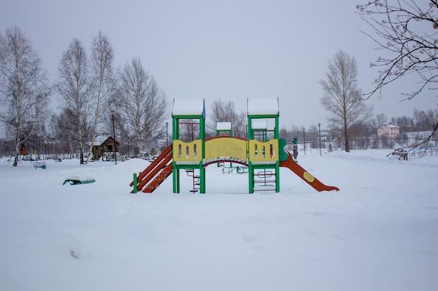Sentieri nel parco invernale. panchina, parco giochi per bambini.