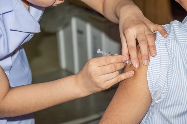 La donna asiatica paziente viene vaccinata