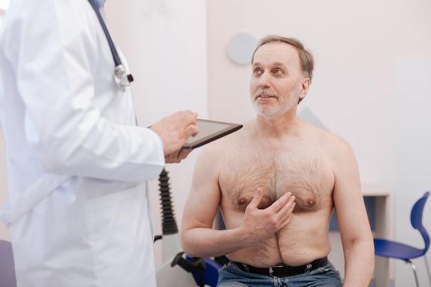 Uomo anziano attento paziente che condivide le sue preoccupazioni per la sua salute mentre era seduto all'ufficio del medico durante il pagamento di una visita regolare