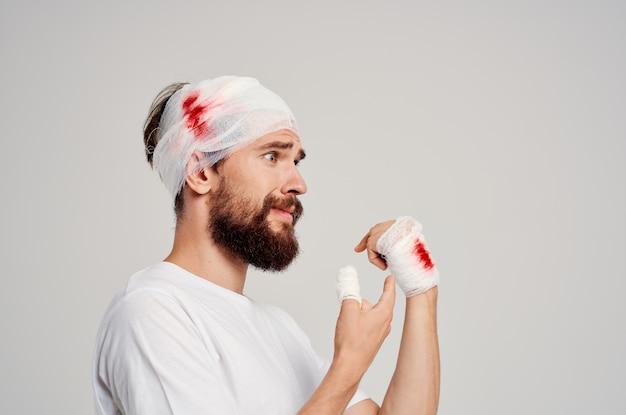 La testa del paziente fasciata e il sangue della mano hanno isolato lo sfondo