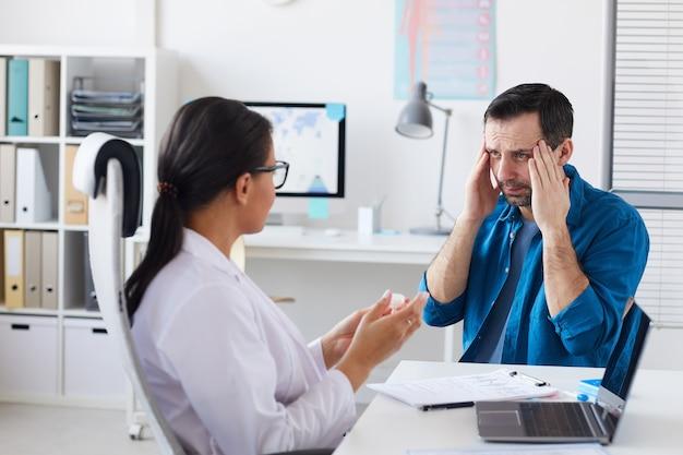 Paziente che si lamenta di mal di testa durante la visita dal medico mentre il medico gli prescrive il medicinale