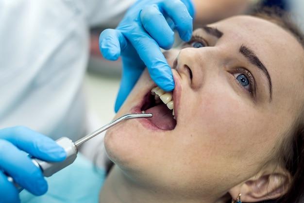Paziente in odontoiatria con strumenti stomatologici, primo piano