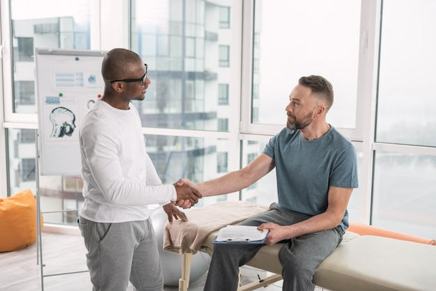 Paziente e medico. bei uomini positivi che si guardano mentre si stringono la mano