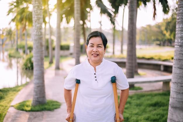 La donna asiatica anziana paziente che usando le grucce sostiene le gambe rotte per la camminata al parco pubblico, concetto di terapia fisica