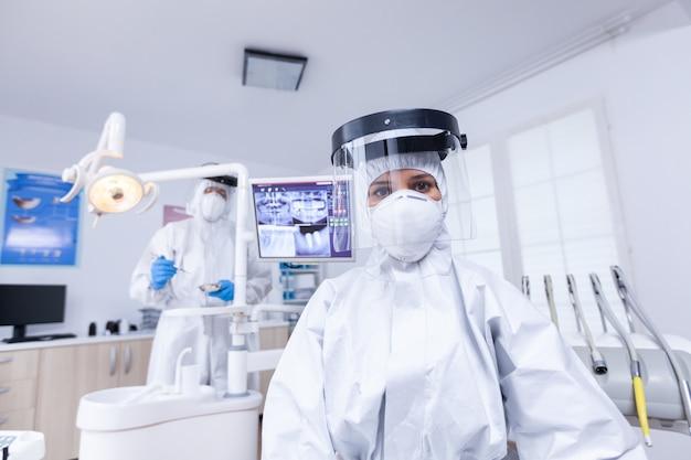 Vista in prima persona del paziente del dentista che guarda in basso in tuta ignifuga covid che tratta i denti. stomatologo che indossa indumenti di sicurezza contro il coronavirus durante il controllo sanitario del paziente.