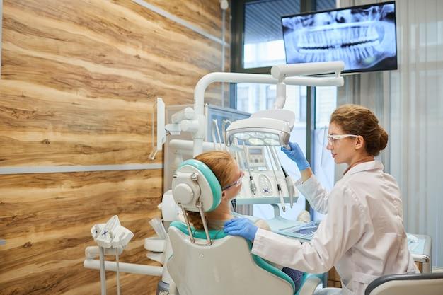 Paziente guardando il monitor con immagine a raggi x davanti a lei mentre il dentista le cura i denti