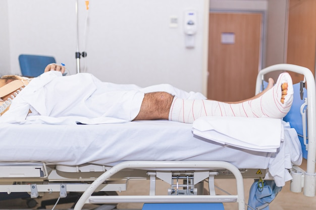 Paziente sdraiato nel letto d'ospedale con gamba rotta. concetto di ricovero e cure mediche.