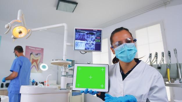 Pov paziente del dentista che spiega la radiografia dentale e la diagnosi per l'infezione dei denti facendo uso della compressa con lo schermo verde. specialista di stomatologia che punta a mockup, copia spazio, display crominanza