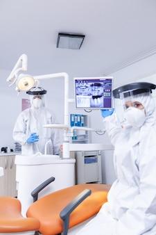 Pov paziente del dentista che spiega la radiografia dei denti dal monitor digitale. specialista in stomatologia che indossa tuta protettiva contro l'infezione da coronavirus che punta alla radiografia.