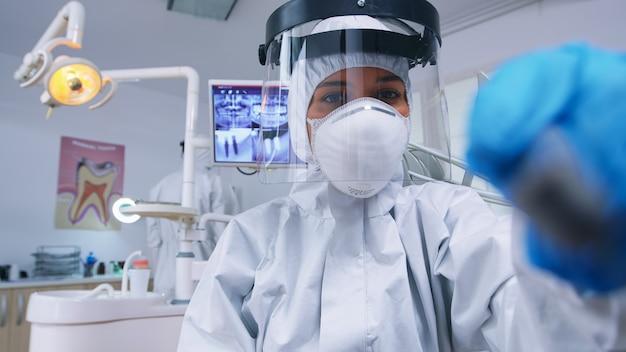 Pov paziente del dentista che tiene strumenti dentali che indossa una tuta di protezione covid che tratta il paziente in una nuova clinica normale. stomatologo che indossa indumenti di sicurezza contro il coronavirus durante il controllo sanitario della persona.