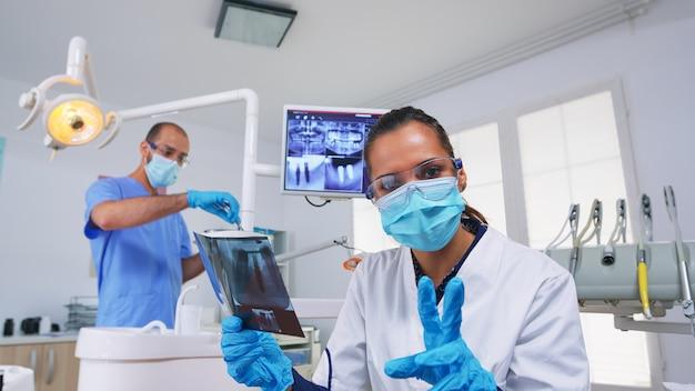 Pov paziente che esamina dentista che chiede i raggi x dentali che mostrano l'immagine dei denti. specialista in stomatologia che indossa una maschera protettiva, lavora nella moderna clinica stomatologica, spiegando la radiografia del dente