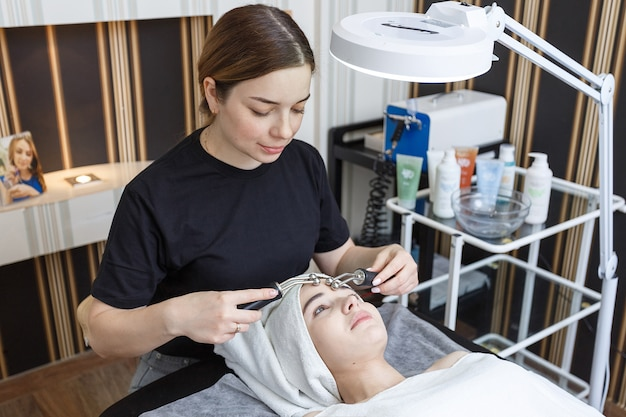 Un paziente riceve un massaggio facciale elettrico dal cosmetologo nella clinica estetica.