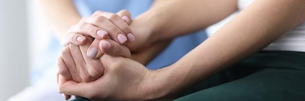 Le mani del paziente e del medico sono giunte insieme.