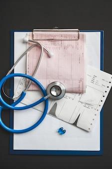 Primo piano della tessera sanitaria di un paziente, uno stetoscopio e pillole sulla scrivania del medico