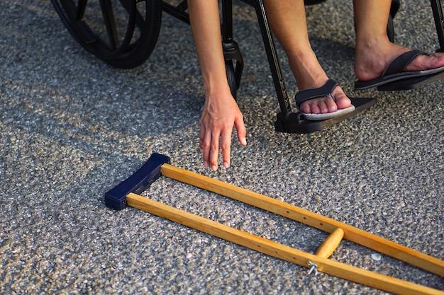 Il paziente seduto su una sedia a rotelle ha raggiunto la sua mano o si è chinato ha raccolto una stampella sul pavimento