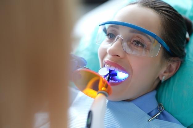 Paziente in visita dal dentista per il controllo regolare e il riempimento dei denti primo piano