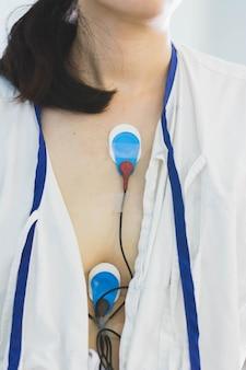 Paziente che indossa un dispositivo di monitoraggio holter per il monitoraggio di un elettrocardiogramma su 24 ore di indagine cardiaca