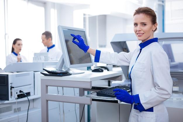 Benessere del paziente. gentile ricercatrice professionista che guarda dritto mentre indica lo schermo e posa in laboratorio