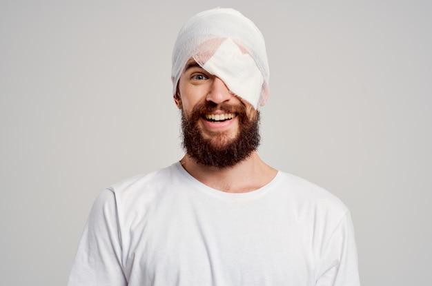 Paziente con una testa fasciata e uno sfondo isolato di sangue oculare