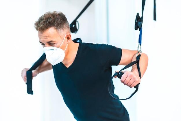 Paziente con maschera facendo stretching. riapertura con misure di sicurezza dei fisioterapisti nella pandemia di covid-19. osteopatia, chiromassaggio terapeutico