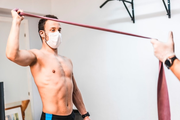 Un paziente con una maschera ha aiutato facendo esercizi con le braccia con il fisioterapista. fisioterapia con misure protettive per la pandemia di coronavirus, covid-19. osteopatia, chiromassaggio terapeutico