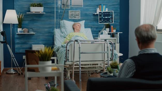Paziente con malattia sdraiato sul letto d'ospedale in casa di cura