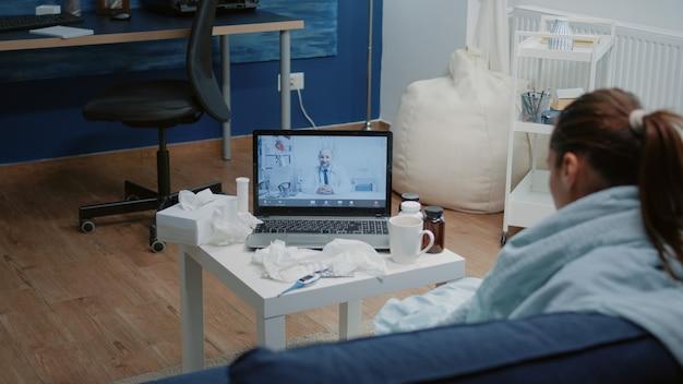 Paziente con malattia che utilizza la videochiamata per la telemedicina sul laptop