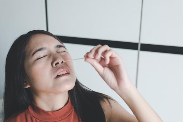 Donna paziente che esegue un kit di test rapido dell'antigene con tampone nasale per il controllo di un covid-19 a casa