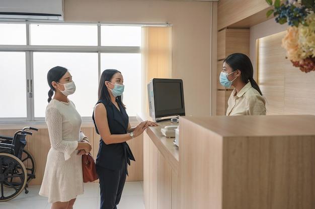 Pazienti che indossano una maschera facciale per il trattamento della malattia con l'addetto alla reception al banco della reception in ospedale
